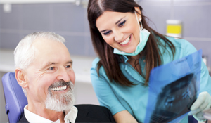 Happy man in a dental chair with his hygienist
