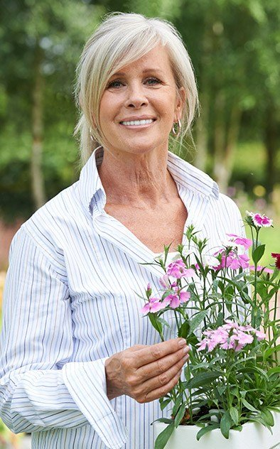 Senior woman outdoors holding flowers