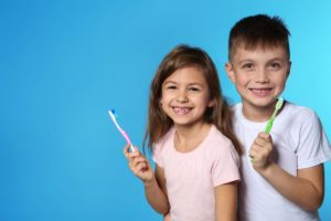 a little girl and boy holding toothbrushes