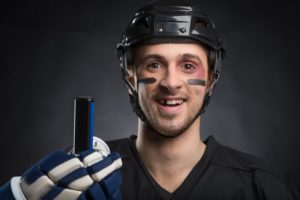 a male hockey player donning his sports attire, complete with a knocked-out tooth