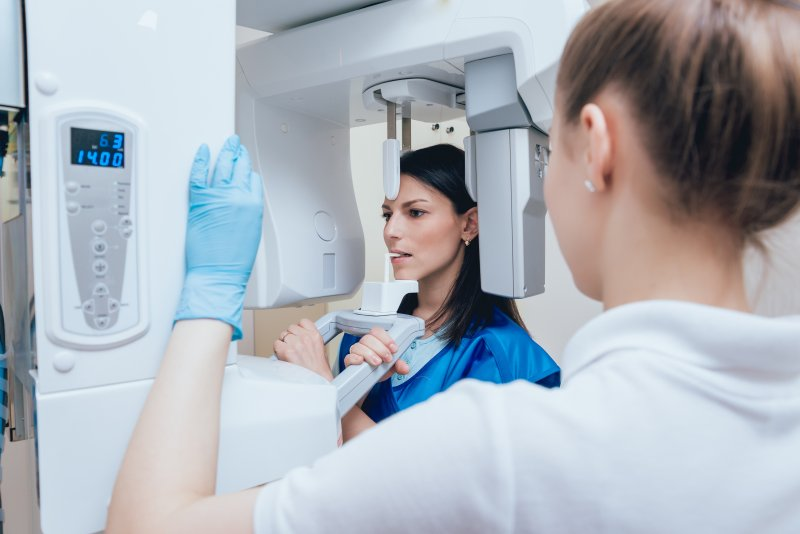 a female patient standing at the CT/Cone Beam Scanner while a hygienist oversees equipment usage