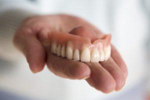 hand holding a denture